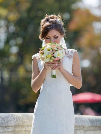 Bride inhales aroma of a bouquet. Portrait of young brunette bride sniffing wedding bouquet at park