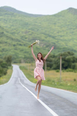 Girl on the asphalt road. Barefoot girl with chamomile bouquet running along road after rain