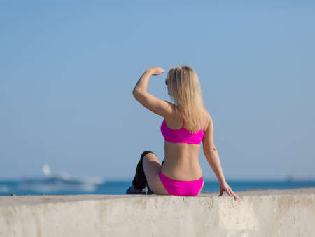 Athletic girl on seafront. Young sportswoman in pink sportswear sits on concrete wall, rear view Stock Photo