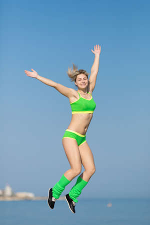 Girl jumping on open air. Young sportswoman in green sportswear and sunglasses jumping with hands raised