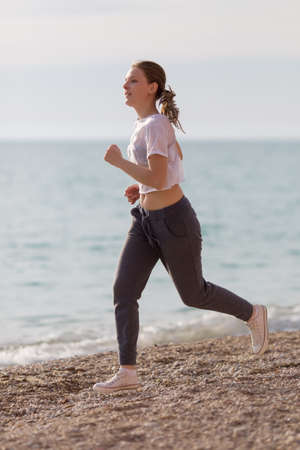 Jogging. Young sportswoman running against the sea in evening time Stock Photo