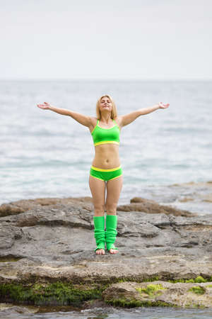 Athletic girl standing with arms raised against the sea. Barefoot young sportswoman in green sportswear doing exercises on rock