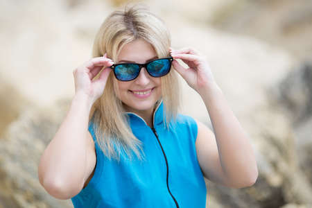 russian ethnicity: Portrait of smiling girl in blue sportswear on open air. Young woman looks through tinted sunglasses at camera