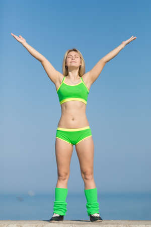 tensed: Athletic girl against a sky. Young sportswoman in green sportswear stands on concrete wall with arms raised and eyes closed
