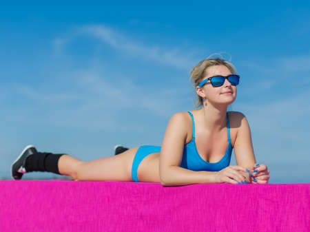 Athletic girl training on open air. Young sportswoman in blue sportswear and sunglasses doing exercises outdoors