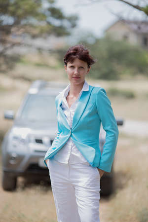 Portrait of girl against her car. Attractive mature woman in white trousers and turquoise jacket posing outdoors