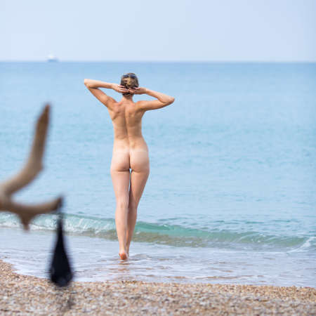 Skinny-Dipping.  Naked young woman enters in sea in cloudy day. Rear view. Square composition Stok Fotoğraf