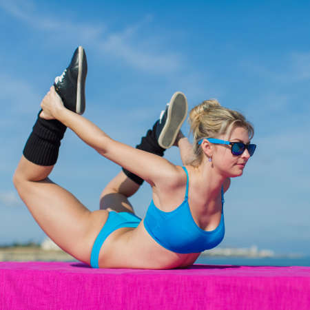 tensed: Athletic girl training on open air. Young sportswoman in blue sportswear and sunglasses doing exercises outdoors, square composition Stock Photo