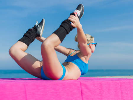Athletic girl training on open air. Young sportswoman in blue sportswear doing exercises outdoors