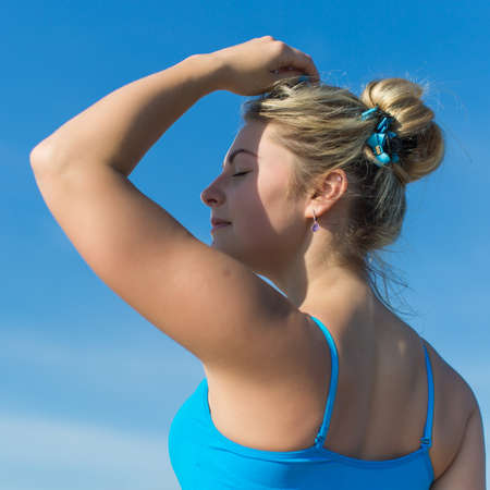 Portrait of young sportswoman against a sky. Athletic girl in blue sportswear posing with eyes closed and arm raised outdoors, square composition