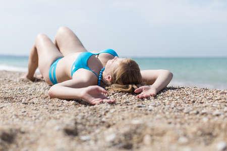 Overgewicht blonde die op kiezelsteenkust zonnebaadt. Volwassen mollige vrouw in blauwe bikini die op terug met opgeheven wapens ligt