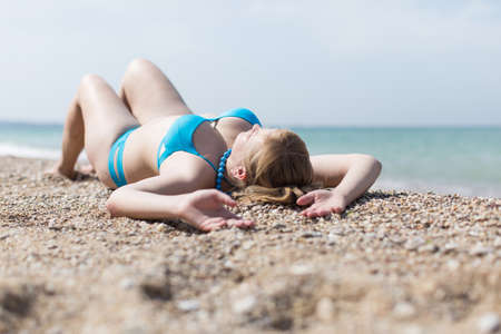 Overweight blonde sunbathing on pebble seashore. Adult plump woman in blue bikini lying on back with arms raised Imagens - 84373726