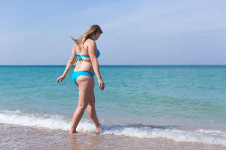 Overweight middle aged woman on sand beach. Overweight woman in blue bikini enters the sea water Фото со стока