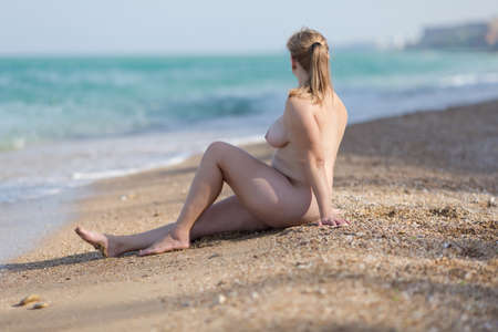Overweight middle aged woman at the sea. Naked overweight woman sits on sand near waters edge Stock Photo