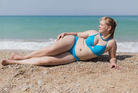 Overgewicht blond aan de zee. Volwassen plump vrouw in blauwe bikini liggend op kiezel tegen de zee Stockfoto