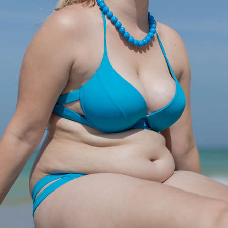 Girl on the beach. Torso of adult woman in blue swimsuit and beads, square composition Stock Photo
