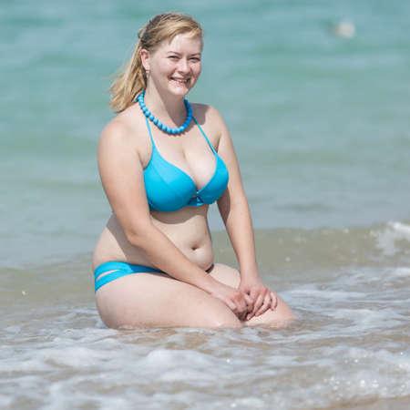 Blonde en surpoids à la mer. Femme adulte en bikini assis dans le bord de l'eau avec les mains sur les genoux et en regardant la caméra en souriant, composition carrée Banque d'images - 84373733
