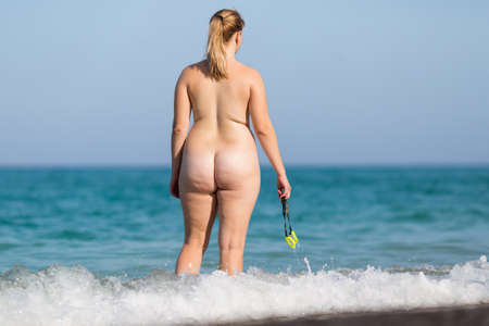Overweight middle aged woman at the sea. Naked mature woman enters the sea water with swimming glasses in hand, rear view Stock Photo
