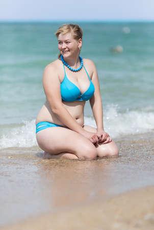 Overgewicht blonde aan de zee. Volwassen vrouw in bikini zitten in waterrand met handen op knieën wegkijken glimlachend