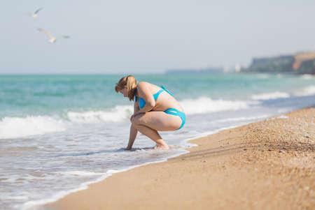 Overgewicht blond aan de zee. Volwassen vrouw in bikini aan zee water op zandstrand aanraken
