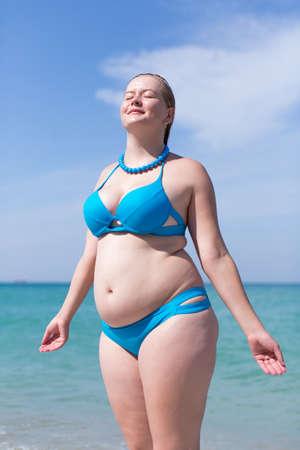Natte vrouw met overgewicht van middelbare leeftijd aan zee. Natte te zware vrouw in blauwe bikini die zich met gesloten ogen bevindt en wapens uitgestrekt tegen overzees Stockfoto
