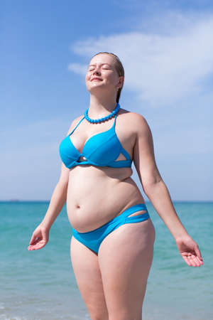 Wet overweight middle aged woman at the sea. Wet overweight woman in blue bikini standing with eyes closed and arms outstretched against sea