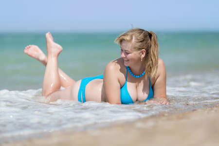 Overweight blonde in surf line. Adult woman in bikini lying on front in sea foam in waters edge Imagens - 84373750