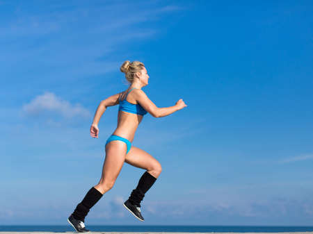 Jogging. Young sportswoman in blue sportswear runs against clear sky Stock Photo