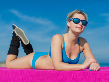 Athletic girl on open air. Young sportswoman in blue sportswear and sunglasses lying down outdoors