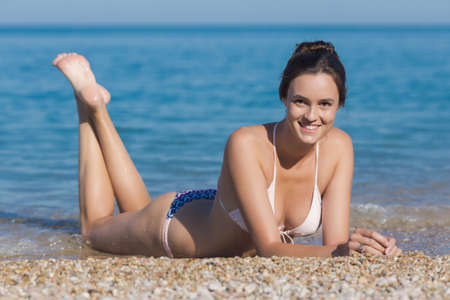 Attractive girl on pebble seashore. Young woman in bikini lying on pebble at waters edge looking at camera smiling