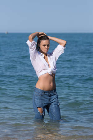 Wet young woman in torn jeans and shirt tied in knot posing in sea. Attractive girl in white shirt tied in knot and ripped jeans stands in sea water with arms raised Reklamní fotografie - 86145487