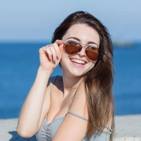not open: Portrait of long-haired woman in sportswear. Attractive girl in sport top with fallen strap looking through sunglasses smiling. Square composition
