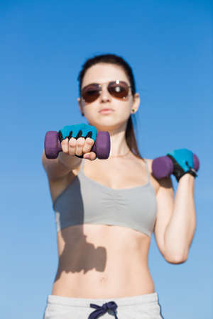 not open: Female fitness outdoors. Portrait of athlete girl with dumbbells on open air. Focus on foreground