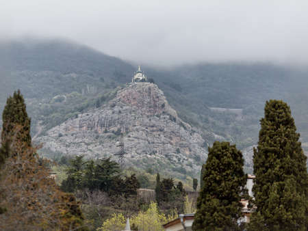 Temple on rock in south mountain area. Landscape with mountains, rock, cypresses and stone church in cloudy day Stock Photo