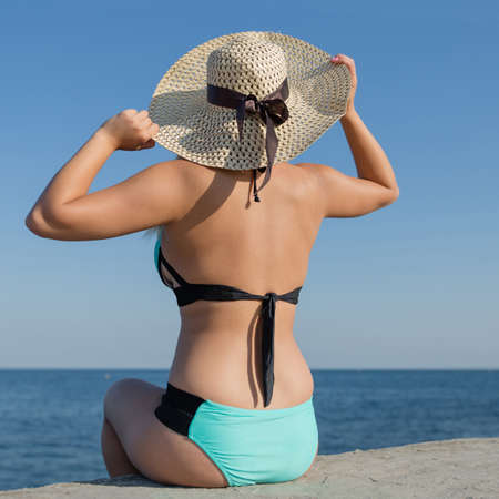 Girl at the sea. Young woman in swimsuit and straw hat sitting on concrete seafront with arms raised, rear view