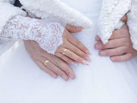Bruiloft handen. Handen van pas getrouwd met trouwringen op vingers tegen witte trouwjurk Stockfoto