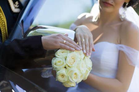 Wedding hands. Groom and bride showing wedding rings on bride bouquet near car 版權商用圖片