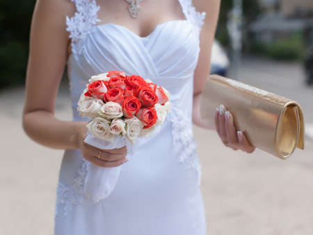 Bride outdoors. Bride in wedding dress with wedding bouquet and reticule in her hands walking on street Stock Photo