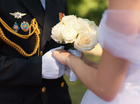 Wedding hands. Hands of the officer in white gloves and hands of his bride with a wedding bouquet from white roses during the wedding ceremony in the fresh air