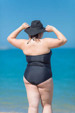 Plus-sized woman in black one-piece swimsuit and black hat stands against the sea with arms raised, rear view