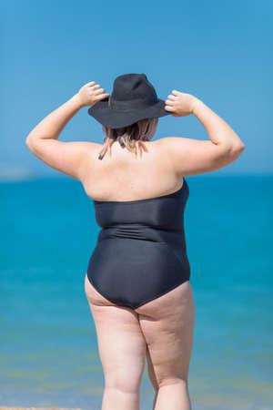 Plus-size vrouw in zwart zwempak uit één stuk en zwarte hoed staat tegen de zee met opgeheven armen, achteraanzicht Stockfoto