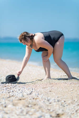 Plus-sized woman in black one-piece swimsuit at the sea