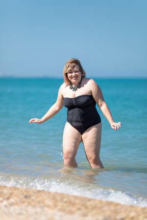 Te zware vrouw in zwart zwempak uit één stuk bij het overzees. Dik meisje komt uit zee kijken camera glimlachen Stockfoto
