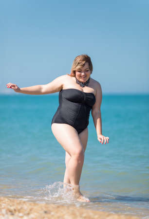 Plus-sized woman in black one-piece swimsuit at the sea. Fat girl comes from sea looking down and smiling