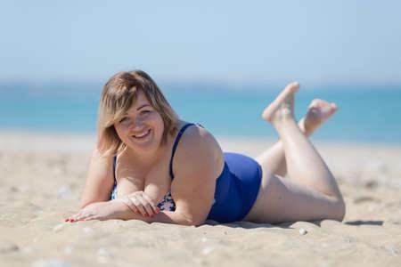 Grote vrouw in blauw zwempak uit één stuk aan zee. Dik meisje in blauwe zwembroek die op zand ligt en camera het glimlachen bekijkt Stockfoto