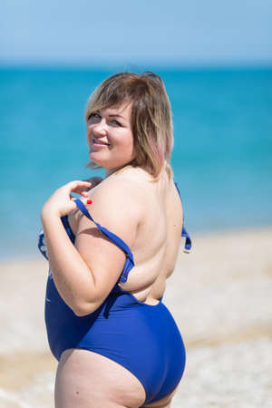 Plus-sized woman in blue one-piece swimsuit at the sea. Fat girl in blue swimwear looking at camera over shoulder and smiling