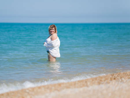 Overweight woman entering in sea. Fat girl in white stands in water looking at camera smiling
