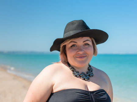 Overweight woman in black swimsuit and black hat posing against the beach. Portrait of fat girl in black swimwear, black hat and black necklace at the sea