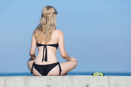 Girl at the sea. Attractive young woman in black bikini with hands on knees rests on seafront, rear view