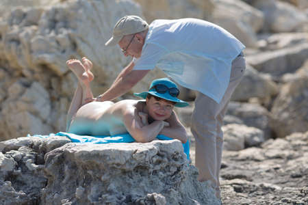 Middle aged family on wild rocky seashore. Man massaging back of his wife on rocky seashores Foto de archivo - 92732759